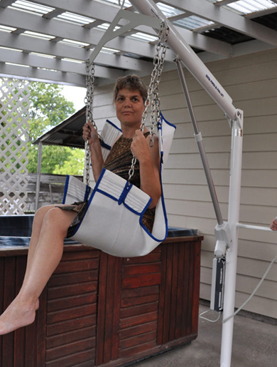 Super power EZ lift shown lifted high towards a hot tub using sling seat, with a user in situ.