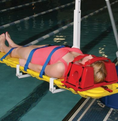 Spineboard attachment for pool lift, shown in use over the pool with patient strapped in